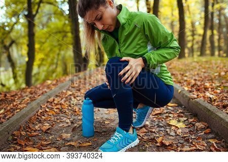 Runner Injured Leg During Training In Autumn Park. Woman Feels Knee Pain Holding It With Hand. Worko