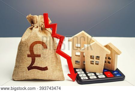 British Pound Sterling Money Bag With Down Arrow And Houses On Calculator. Falling Real Estate Marke