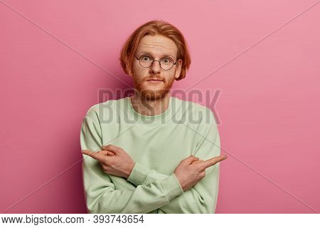 Presentation, Advertising, Choice Concept. Unsure Bearded Redhead Man Points Reft And Right Corners,