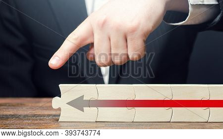 Man Points His Finger At The End Of The Puzzle Chain With An Arrow. Continuation Of The Process Of G