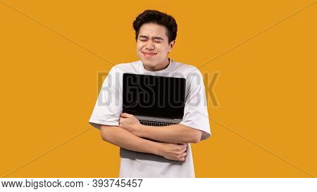 Technology Lover Concept. Happy Excited Asian Man Hugging Laptop With Black Blank Empty Screen, Hold
