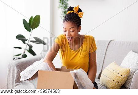 Happy Customer Concept. Portrait Of Excited Black Woman Opening And Unpacking Cardboard Box Parcel,