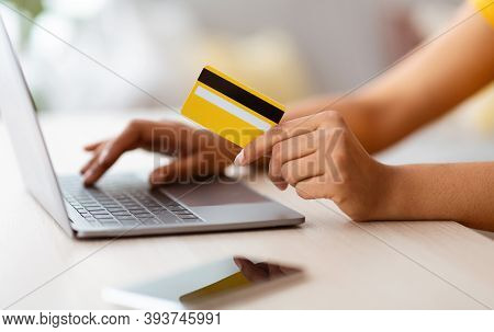Modern Shopper. Side View Closeup Of Unrecognizable Black Lady Showing Credit Card And Using Laptop