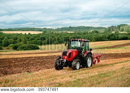 Red Tractor Plowing In Autumn, Farmer Plowing Stubble Field In Tractor Preparing Plows The Land, Agr