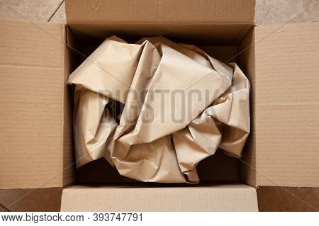 Crumpled Wrapping Craft Brown Paper In Open After Delivery Paperboard Box. Horizontal. Delivery, Eco