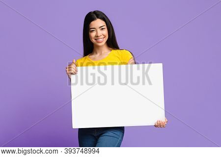 Smiling Asian Female Holding Blank White Placard In Hands, Demonstrating Copy Space For Your Text Or