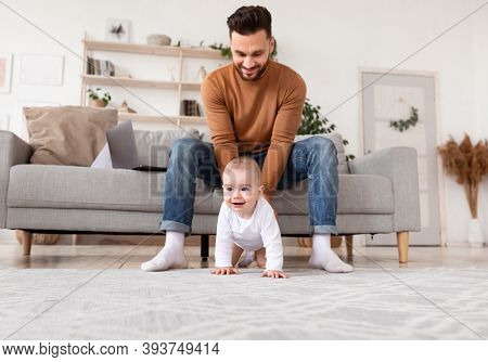 Cheerful Young Dad Looking At His Baby Daughter Toddler As She Crawling On Floor At Home. Father Car