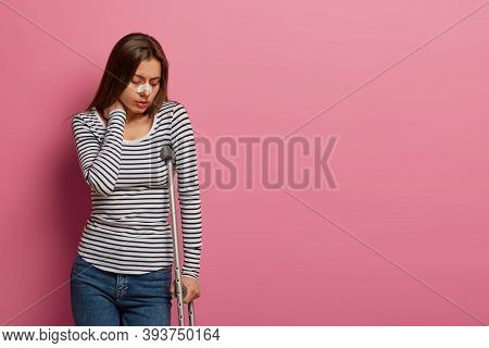 Isolated Shot Of Unhappy Woman Focused Down, Touches Neck From Pain, Suffers After Terrible Incident