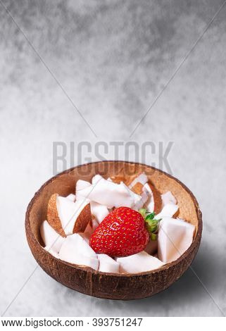 A Bowl Of Coconut Pieces And Strawberry On Concrete Background. Coconut Ingredient On Plate. Vegan O