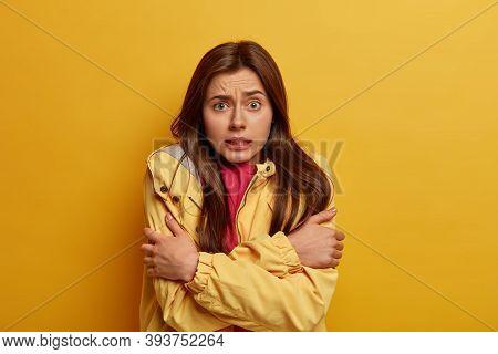 Dissatisfied Brunette Woman Feels Cold, Hugs Herself To Warm Up, Wears Raincoat, Has Walk During Rai