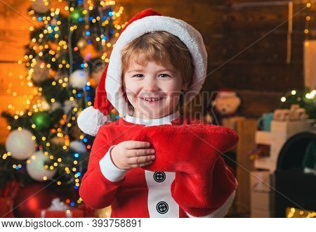 Childhood Moments. Child Cheerful Face Got Gift In Christmas Sock. Check Contents Of Christmas Stock