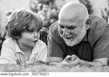 Happy Grandfather And Grandson Relaxing Together. Fathers Day. Cute Boy With Dad Playing Outdoor. Tw