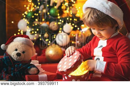 Christmas Kid. Happy Little Smiling Boy With Christmas Gift Box. Happy Child Holding A Red Gift Box