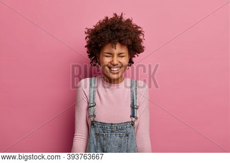 Positive Young Afro American Girl Smiles Broadly, Has Upbeat Mood, Laughs At Something Very Funny Or