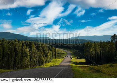 Beautiful View Of A Scenic Road, Alaska Hwy, In The Northern Rockies. Colorful Blue Sky With Clouds.