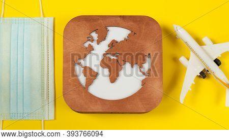 Plane Model, Face Mask, Loupe And Earth Model On A Yellow Background. Flight Impact Of Coronavirus (