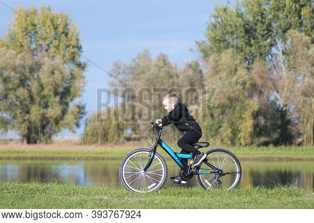 The Happy Boy Is Riding A Bike On Lakeshore In Nature.