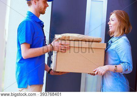 Smiling Delivery Man In Blue Uniform Delivering Parcel Box To Recipient - Courier Service Concept. S