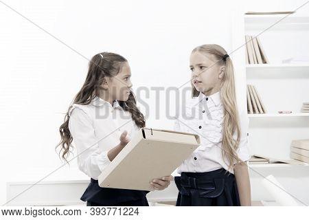 Needing Homework Help. Adorable Small Children Holding File With Homework In Classroom. Doing Homewo