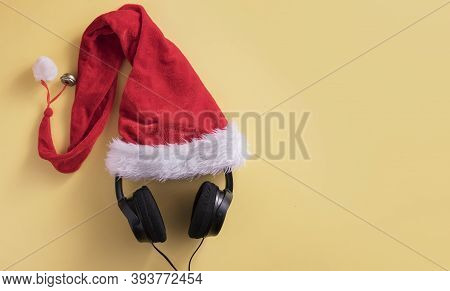 Flat Lay Composition With Headphones And Santa Claus Hat On Colored Background With Copy Space. Chri