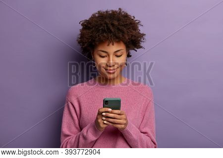 Smiling Dark Skinned Woman Browses Internet On Mobile Phone, Types Something In Mobile Display, Uses