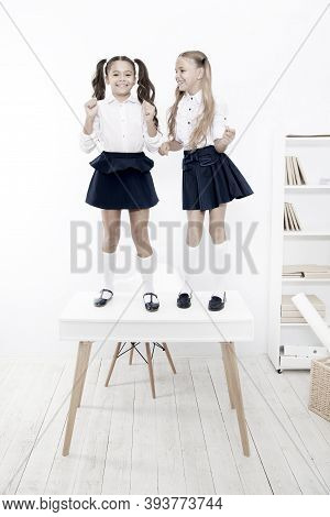 Back To School Style. Happy Small Girls With Long Hair Styles Standing On Desk In Class. Little Chil