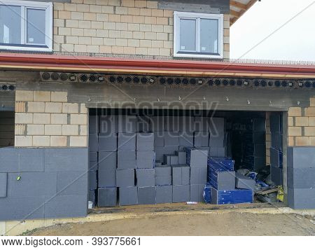 House Under Construction With Garage Filled With Graphite Polystyrene Boards For House Thermal Insul