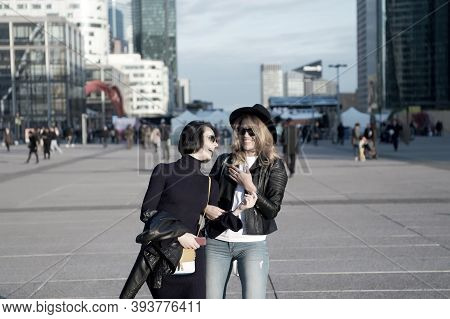 Happy Girls Walk In Business District Of La Defense, Paris. Women Smile In Fashionable Clothes On Su