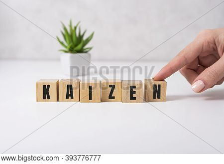Kaizen Improvement Sign Made Of Blocks On A Wooden Desk In A Bright Room