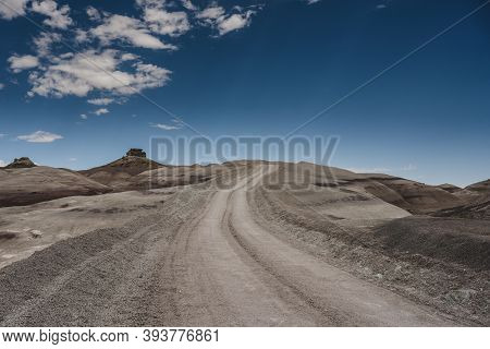Dirt Road Cuts Into Desert Ground On Blue Sky Say