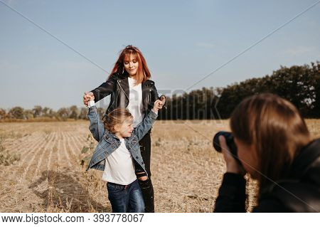 Daddy Taking Pictures Of His Family. Young Man Photographing His Wife And Little Daughter For Family