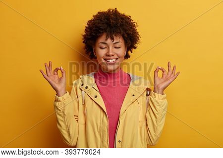 Concentrated Cheerful Curly Woman Keeps Both Hands In Okay Gesture, Meditates Indoor, Has Eyes Close