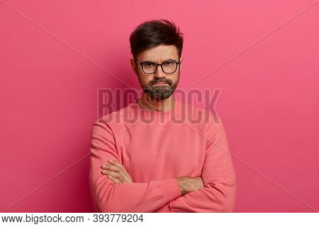 Disappointed Displeased Bearded European Man Crosses Arms And Presses Lips, Expresses Resentment And