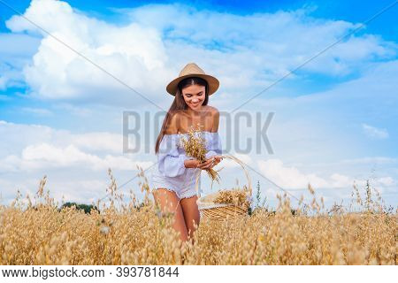 Young Beautiful Woman With Straw Hat On The Head Standing At Golden Oat Field Holding Basket With Ea