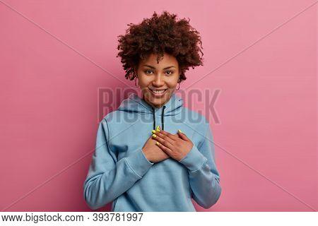 Pretty Smiling Afro American Woman Makes Grateful Gesture, Appreciates Heartwarming Words, Wears Cas