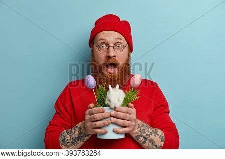 Impressed Wondered Bearded Hipster Guy Holds Pot With Small White Fluffy Easter Bunny And Decorated