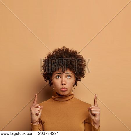 Unhappy Curly Haired Woman Dislikes Something, Points Above, Purses Lower Lip, Has Gloomy Face Expre