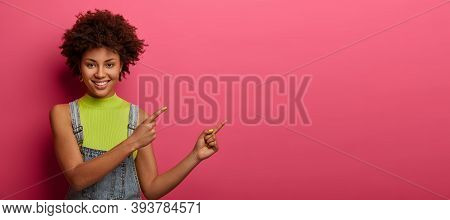 Studio Shot Of Smiling Curly Woman Wears Bright Vest And Dungarees, Points Both Index Fingers At Upp