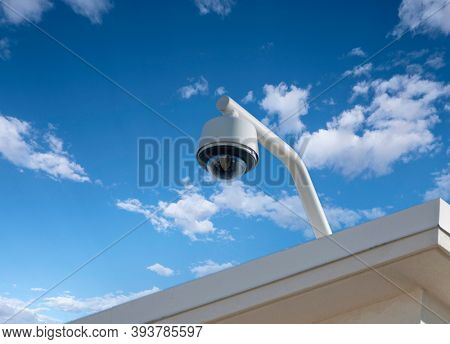 Rooftop security camera with cloudy sky.