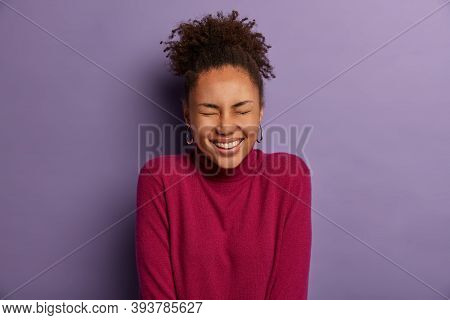 Photo Of Optimistic Curly Woman With Dark Skin, Closes Eyes And Smiles Broadly, Shows White Teeth, F