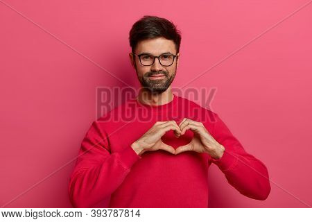 My Heart Belongs To You. Romantic Handsome Bearded Man Makes Heart Shape Symbol With Fingers, Falls