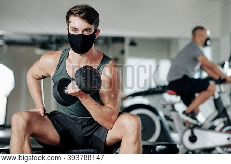 Portrait Of Handsome Young Fit Man In Textile Mask Sitting On Gym Bench With Heavy Dumbbell In Hands