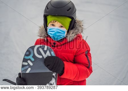 Little Cute Boy Snowboarding Wearing A Medical Mask During Covid-19 Coronavirus. Activities For Chil