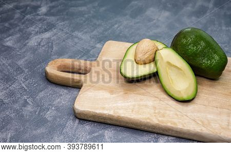Ripe Avocado Cut In Half On A Table. Avocado Is Cutting In The Middle On A Wooden Cutting Board. Raw