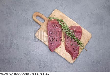 Raw Pork Steak With And Herbs. Sliced Beef Steak With Rosemary, Salt And Black Pepper On A Table Pre