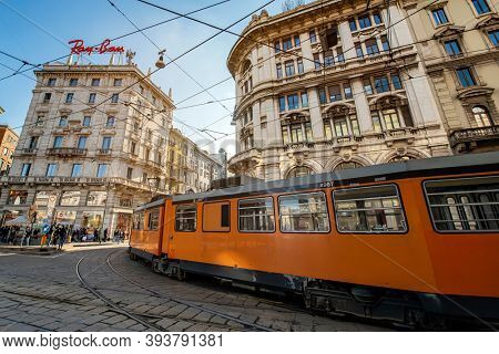 Milano, Italy - oct 16, 2020: Orange tram on the streets and Ray Ban brand commercial signal on the top of  Milano, Italy