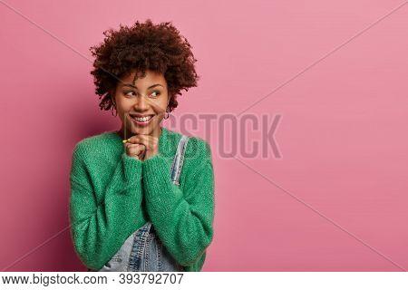 Headshot Of Dark Skinned Woman Looks Aside, Has Tender Smile, Keeps Hands Under Chin, Wears Green Sw