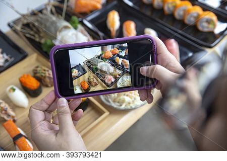 Woman Photographing Food Served Japanese Sushi Set , Sushi Nigiri Rolls And Sashimi In Japanese Food