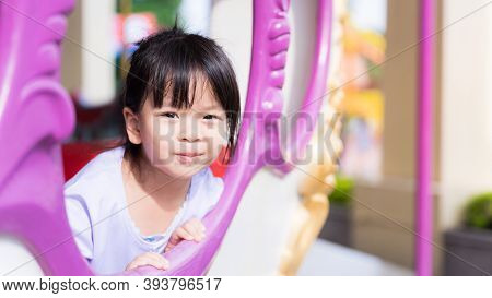 Healthy Girl Sits In A Carousel At An Amusement. Sweet Smiley Child Wearing A White Dress. Warm Suns