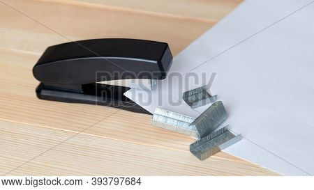 Stapler And Staples With Sheets Of Paper A Wooden Table.